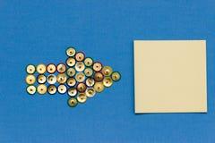 Flecha hecha de los pasadores coloreados que apuntan el papel de nota Fotos de archivo libres de regalías
