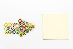 Flecha hecha de los pasadores coloreados que apuntan el papel de nota Foto de archivo