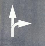 Flecha pintada en el asfalto Foto de archivo libre de regalías