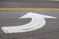 Flecha pintada en la calle del asfalto Imagen de archivo