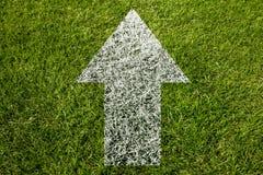 Flecha que señala encima de símbolo en hierba Imágenes de archivo libres de regalías