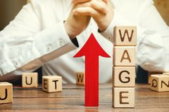 Flecha roja para arriba cerca de bloques de madera con el salario de la palabra y un hombre de negocios Concepto del aumento sala imagen de archivo