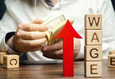 Flecha roja para arriba cerca de bloques de madera con el salario de la palabra y un hombre de negocios Concepto del aumento sala foto de archivo libre de regalías