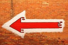 Flecha roja pintada en una pared de ladrillo Fotografía de archivo libre de regalías