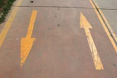 Flechas amarillas de la dirección en el camino Imagen de archivo libre de regalías