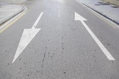 Flechas de la dirección en el asfalto Imágenes de archivo libres de regalías