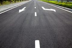Flechas de las muestras de camino en superficie asfaltada fotos de archivo libres de regalías
