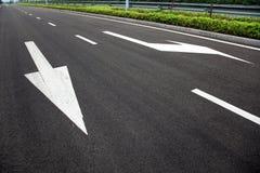 Flechas de las muestras de camino en superficie asfaltada Imágenes de archivo libres de regalías