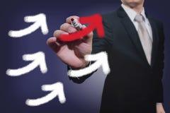 Flechas de levantamiento del gráfico del hombre de negocios Fotografía de archivo libre de regalías