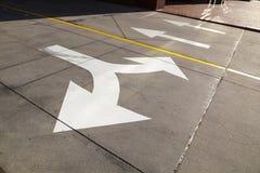 Flechas en el asfalto para indicar la dirección de la conducción Imagenes de archivo