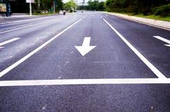 Flechas en el asfalto para indicar la dirección de la conducción Imagen de archivo