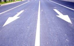Flechas en el asfalto para indicar la dirección de la conducción Fotos de archivo