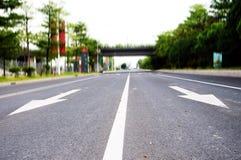 Flechas en el asfalto para indicar la dirección de la conducción Imagen de archivo libre de regalías
