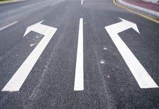 Flechas en el asfalto para indicar la dirección de la conducción Foto de archivo libre de regalías