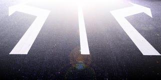 Flechas en el asfalto para indicar la dirección de la conducción Imágenes de archivo libres de regalías
