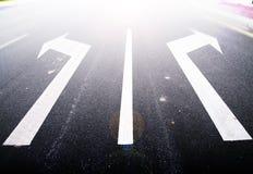 Flechas en el asfalto para indicar la dirección de la conducción Fotografía de archivo libre de regalías