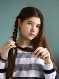 Flechtendes langes braunes Haar des Zopfs des hübschen Mädchens des Jugendlichen Lizenzfreies Stockfoto