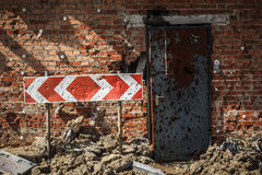 Flecked with shrapnel brick wall, door and sign Royalty Free Stock Photos
