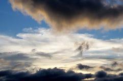 Flecken von Weißwolken zwischen dunklem cloudscape Stockbild