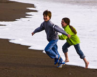 Flee. Two children running on a beach on a chilly day Stock Photos