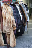 Flee Market - fur coats. Fur coats on display on a metal bar at a flee market in berlin kreuzberg, germany: typical street scene of berlin stock photos
