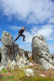 Flee from one rock to another. Young man in flee from one rock to another - low angle, against sky. Shot in Hottentots-Holland Mountains nature reserve, near Stock Photo