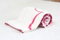 Fleece blanket. Small fleece blanket on white bed Royalty Free Stock Images