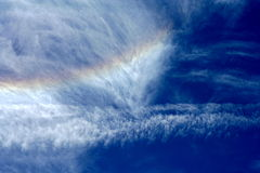Fleecy clouds and rainbow Stock Images