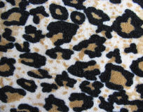 Fleecy white and brown leopard skin fabric stock images