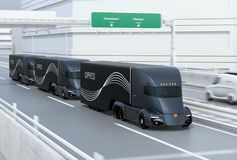 A fleet of black self-driving electric semi trucks driving on highway. 3D rendering image royalty free illustration