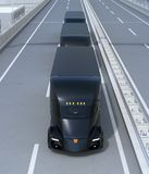 A fleet of black self-driving electric semi trucks driving on highway Royalty Free Stock Photo