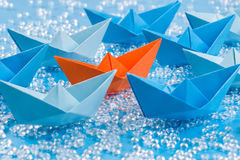 Fleet of blue Origami paper ships on blue water like background surrounding an orange one. Fleet of blue Origami paper ships on blue waterlike background royalty free stock images