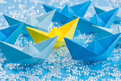 Fleet of blue Origami paper ships on blue water like background surrounding a yellow one. Fleet of blue Origami paper ships on blue waterlike background royalty free stock image