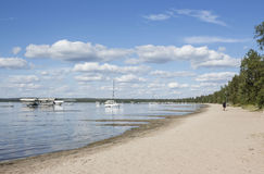 Fleet of boats coasting in the lake next to a sandy beach. Horizontal image of a fleet of boats and ships floating in the lake next to a sandy beach under a Royalty Free Stock Photo
