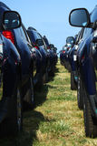 Fleet of new cars ready to ride. Lots of same cars parked on green grass with a blue sky background Royalty Free Stock Photography
