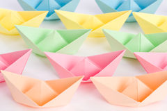 Fleet of origami paper ships passing by Stock Images