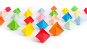 Fleet of origami paper ships in triangle shape isolated on white Stock Photography