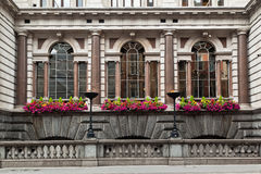 Fleet Street Historical Building London. The facade of a historical building with blooming flowers and arch windows with marble columns, Fleet Street, downtown Royalty Free Stock Images