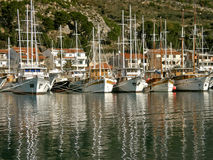 Fleet of tourist boats. The fleet of traditional tourist wooden boats anchored in the harbor an their reflection in Adriatic sea. Horizontal color photo stock image