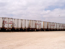 Fleet of trucks. Rear view of fleet of trucks or lorries parked in row with cloudscape background Stock Photo