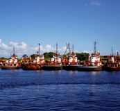 Tugboat fleet parked in the dock stock photos