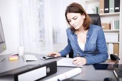 Fleißige Geschäftsfrau, die einen Bericht schreibend sitzt Lizenzfreies Stockfoto