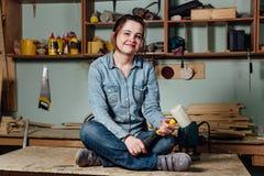 Fleißige Mitte des Porträts alterte erwachsene professionelle weibliche Tischlerarbeitskraftwerkstatt oder -garage lizenzfreie stockfotografie