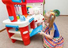 Fleißiges kleines Mädchen, das Lebensmittel im Spielzeugofen für ihren Teddybären kocht Lizenzfreies Stockfoto