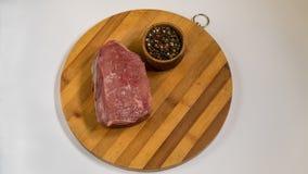 Fleisch auf einem hölzernen Brett Gewürze und Rindfleisch lizenzfreie stockbilder