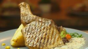Fleisch des Rindfleisches und des Schweinefleisch auf einem Knochen grillte Grill zusammen mit Kartoffelpürees und Gemüse dreht s stock footage