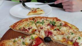 Fleisch fressend eine köstliche frisch gebackene Pizza mit Käse, Mais, Tomaten, Fleisch und Kräutern in einem stilvollen weißen H stock video