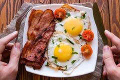 Fleisch fressend sein Frühstück von durcheinandergemischten Eiern, Speck Stockbilder