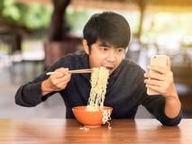 Fleisch fressend, während, Smartphone schauend und mit Lizenzfreie Stockfotografie