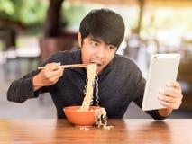Fleisch fressend, während, Tablette schauend und mit stockbilder